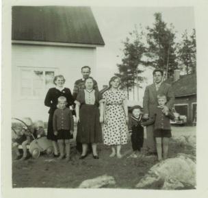 Vasemmalla kärryissä Tuula ja Leena, seisomassa Toini, Hannu, Onni, Liida, Anja, Ismo, Reino ja Markku. Valokuva otettu Onnin rakentaman talon edustalla, Lievestuoreella.